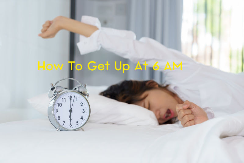 Woman stretching and yawning while waking up in the morning with alarm clock
